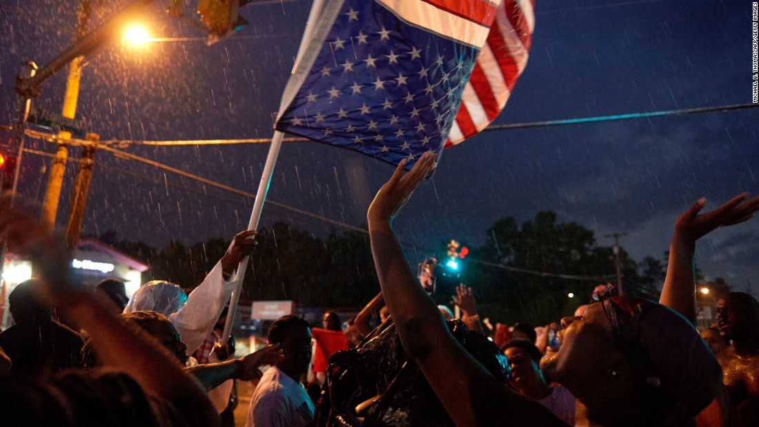 Protesters march in the rain in Ferguson on August 9.