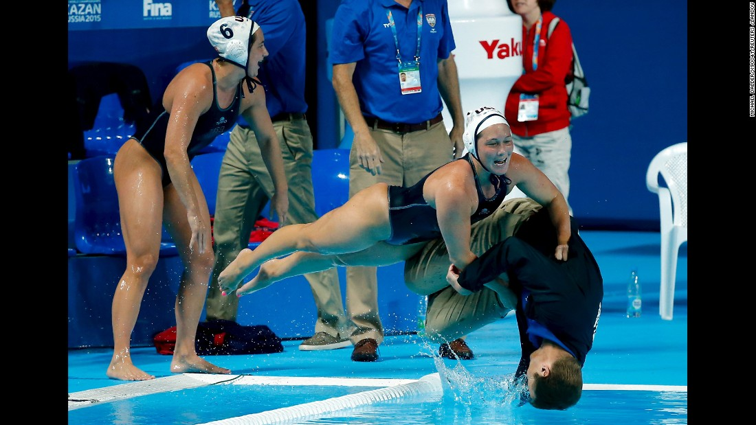 U.S. water polo players push head coach Adam Krikorian into the pool after they defeated the Netherlands in their women's water polo gold medal match during the Aquatics World Championships in Kazan, Russia, on Friday, August 7.