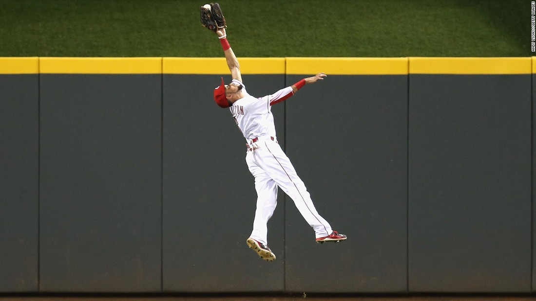 Billy Hamilton of the Cincinnati Reds leaps to catch the ball hit by Jason Heyward of the St. Louis Cardinals in the eighth inning on Tuesday, August 4, in Cincinnati, Ohio.