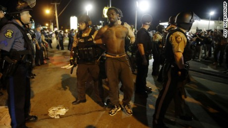 St. Louis County Police make an arrest along West Florissant Avenue, Monday, Aug. 10, 2015, in Ferguson, Mo. Ferguson was a community on edge again Monday, a day after a protest marking the anniversary of Michael Brown's death was punctuated with gunshots. (AP Photo/Jeff Roberson)