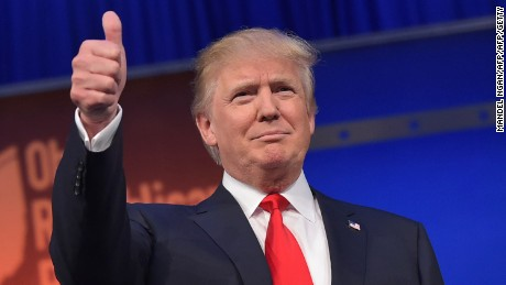 Donald Trump flashes a thumbs-up as he arrives for the start of the prime time Republican presidential debate on August 6, 2015 at the Quicken Loans Arena in Cleveland, Ohio.
