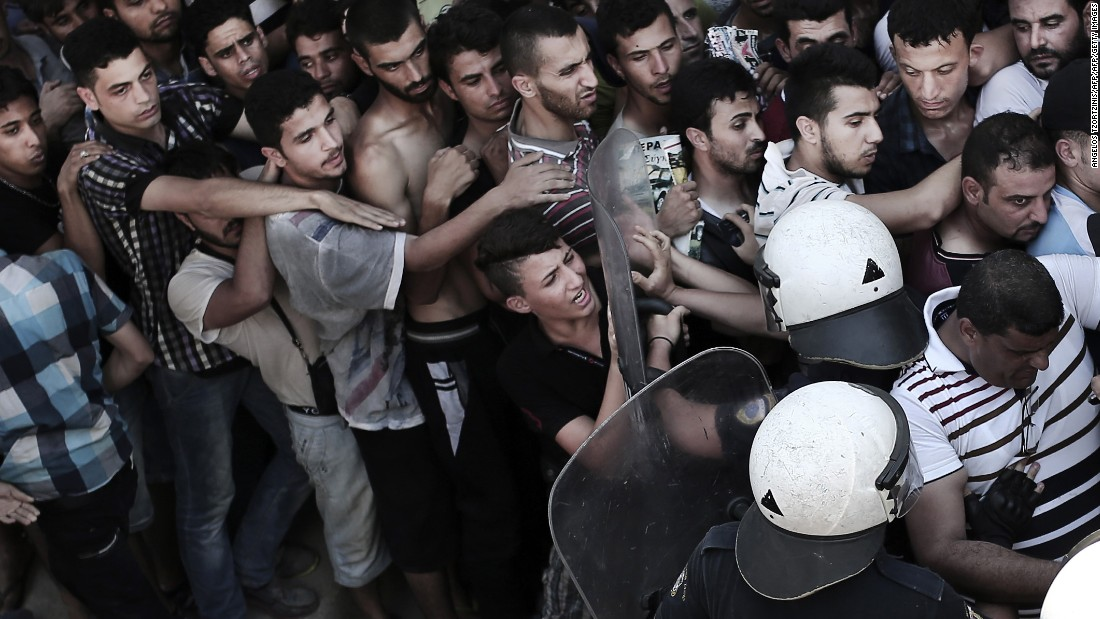 A policeman pushes a man as hundreds wait to complete registration at a stadium in Kos on August 12.