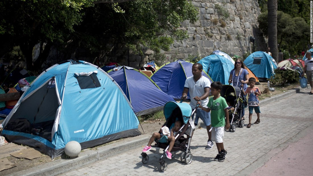 People walk past tents set up in a street in Kos on August 10.