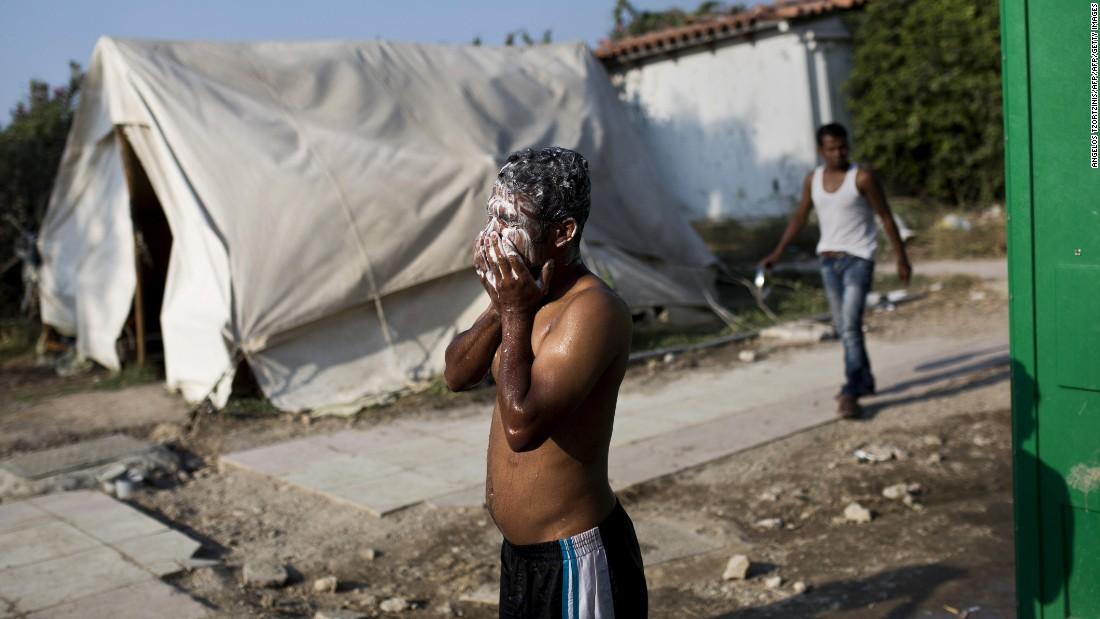 A man washes his face near a deserted hotel in Kos where hundreds of migrants found temporary shelter on August 10.