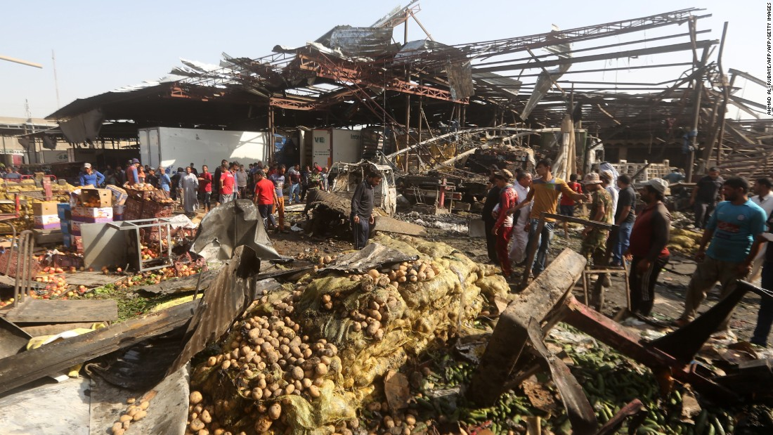 Iraqi men look at damage following a bomb explosion that targeted a vegetable market in Baghdad on Thursday, August 13. ISIS claimed responsibility for the attack.