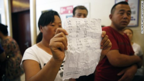 A woman (C) holds a name list of missing firefighters as family members talk to media to seek for help after being barred from a press conference authorities have at a hotel in Tianjin on August 15, 2015. Furious, frustrated and fearful, relatives of the missing in giant explosions in Tianjin besieged officials on August 15 demanding answers on their loved ones's fates- only for security to intervene instead.CHINA OUT     AFP PHOTO        (Photo credit should read STR/AFP/Getty Images)