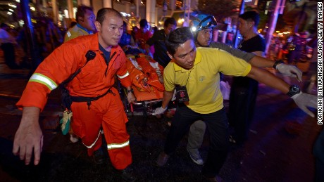 Thai rescue workers carry an injured person after a bomb exploded outside a religious shrine in Bangkok on Monday, August 17.