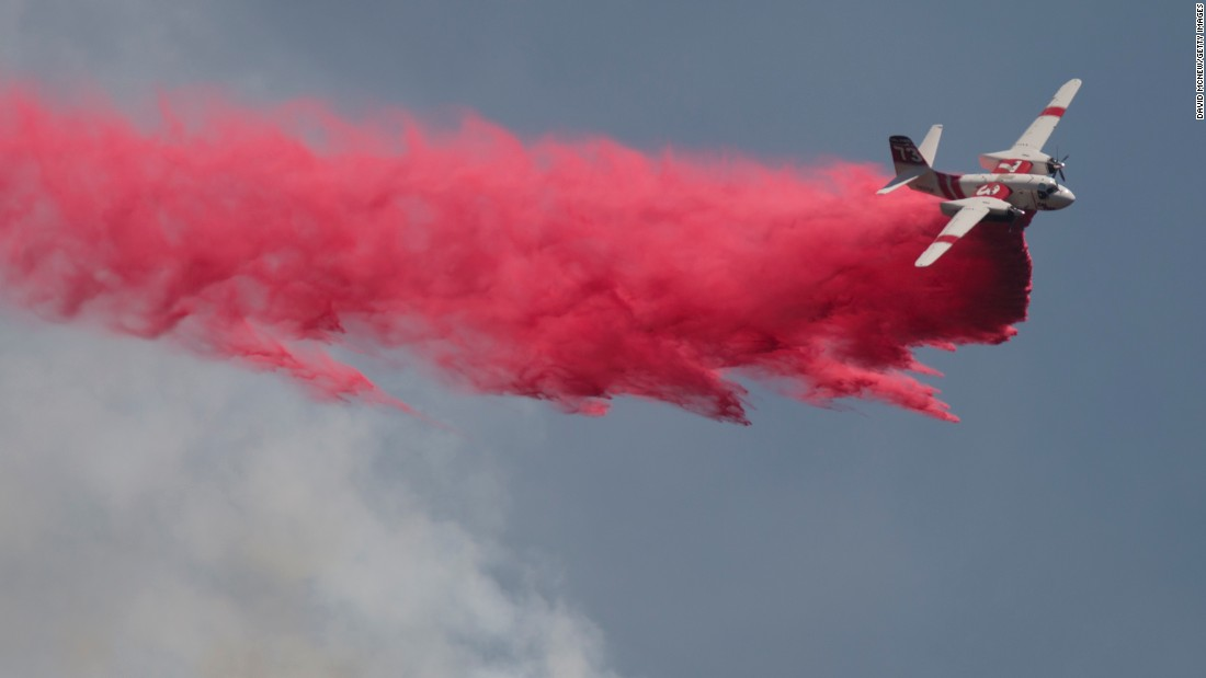 A plane drops fire retardant on the Cabin Fire north of Asuza, California, on Saturday, August 15.