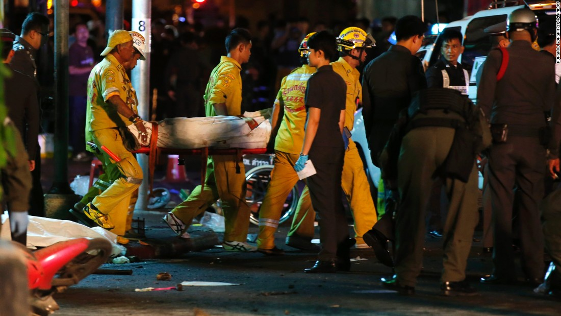 Rescue workers carry the body of a victim away from the scene.