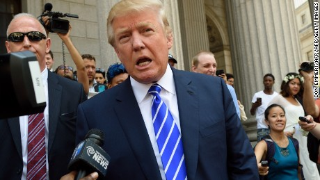 US presidential candidate Donald Trump exits New York Supreme Court after morning jury duty August 17, 2015 in New York.  Trump reported for jury duty in New York on Monday, stepping out of a sleek black limo to be mobbed by media and supporters. The bombastic real estate magnate, who is leading the polls among 17 Republican candidates for president, arrived at New York State Supreme Court at 9:08 am (1308 GMT) dressed in a blue suit and striped tie. He strode up the sweeping steps of the court house surrounded by a phalanx of police, television cameras, journalists and photographers, signing an autograph for one fan and fist-bumping another.  AFP PHOTO/DON EMMERT        (Photo credit should read DON EMMERT/AFP/Getty Images)