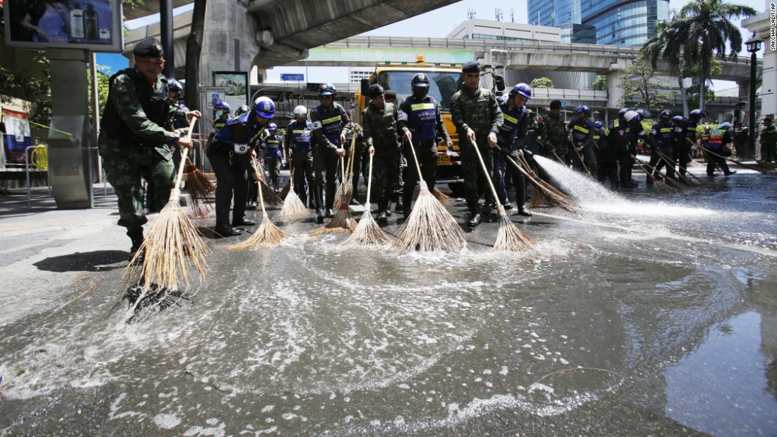 Police and soldiers wash the street in front of the Erawan Shrine.