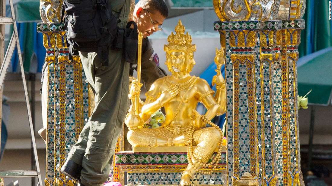 Police investigators work near the statue of Phra Phrom, the Thai interpretation of the Hindu god Brahma, at the Erawan Shrine the morning after the explosion.