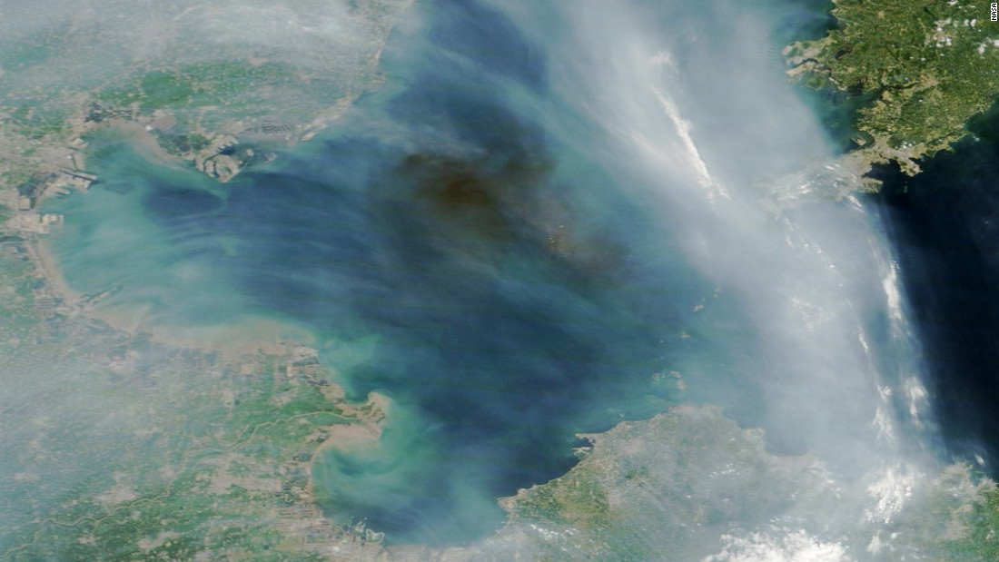 A dark plume of smoke drifts over the Bohai Sea off the east coast of China. The source of the smoke appears to be industrial fires caused by explosions at a port in Tianjin, China. The streams of light gray smoke in the image likely were caused by wildfires in eastern China. NASA's Terra satellite captured the images at 2:30 Universal Time (10:30 a.m. local time) on August 13, 2015.