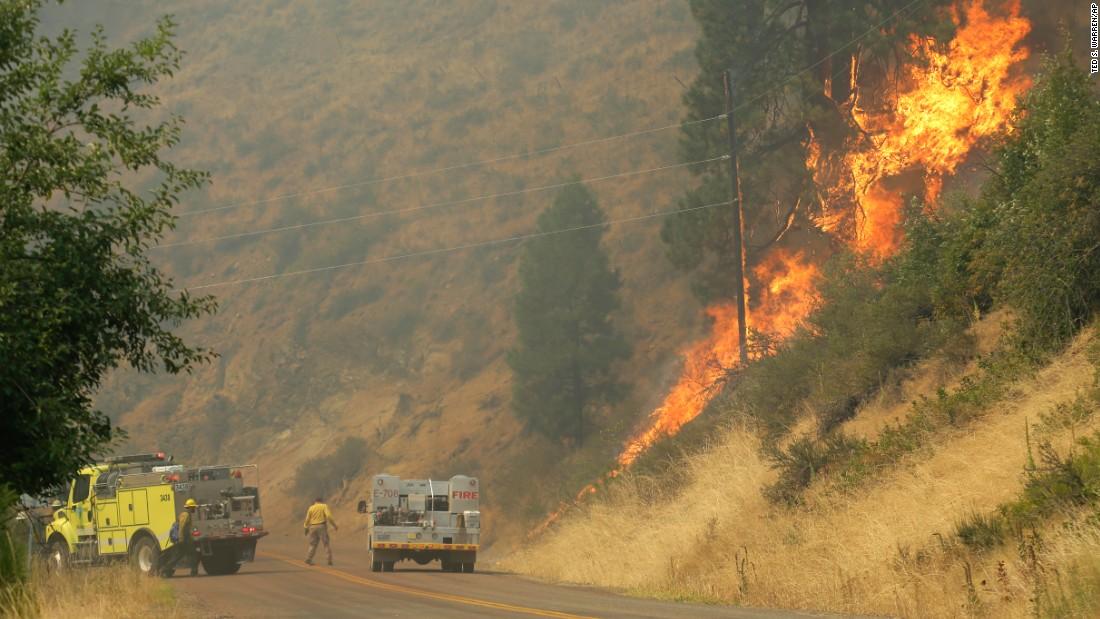 Firefighters battle a wildfire on a hillside in Twisp on August 20.