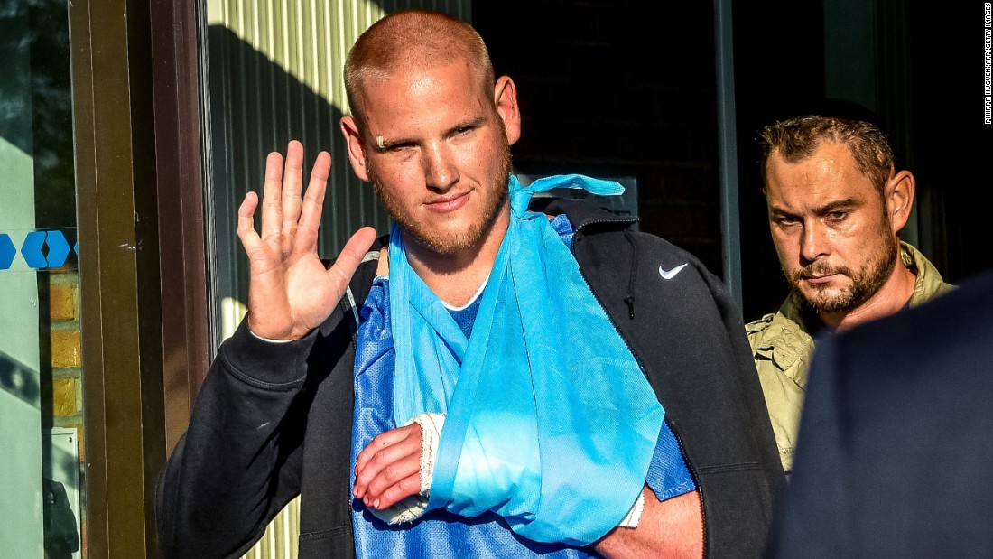Spencer Stone, one of the passengers who overpowered the gunman who had an assault rifle on a high-speed train, gestures as he leaves the hospital of Lesquin, northern France, on Saturday, August 22. On August 21, a gunman opened fire on the train traveling from Amsterdam to Paris, injuring two people before being tackled by several passengers. Stone, an off-duty member of the U.S. Air Force, was first to the gunman, who slashed him in the neck and almost sliced off his thumb with a box utter.