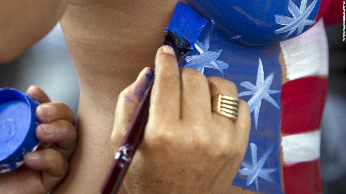Women who pose for tips wearing body paint and underwear help each other get ready in New York's Times Square on Wednesday, August 19. New York City recently created a task force to examine how it can rein in topless women who officials say are aggressively soliciting tips after posing for pictures with tourists.