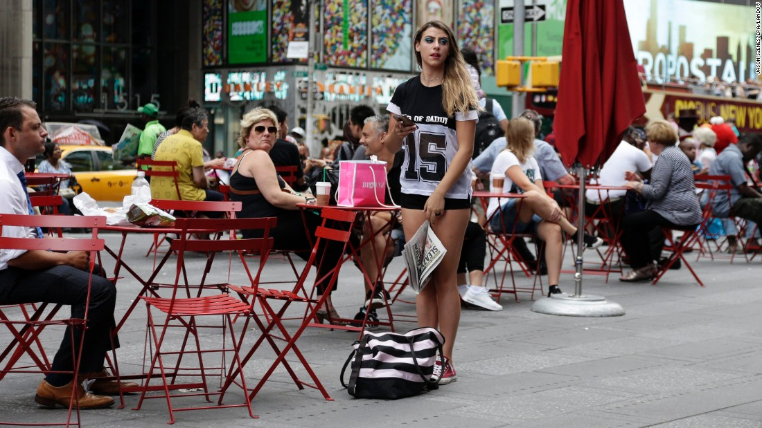 A street performer waits for her handlers before she walks around seminude in Times Square on August 19.