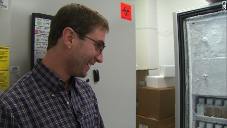 Eric, a poop donor for OpenBiome, looks at bottles of frozen fecal transplants he helped create.