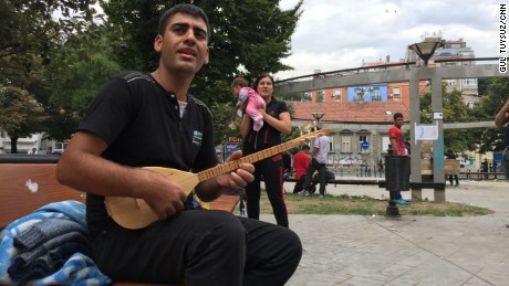 """Hejar Hasan, 24, from Qamishli, Syria sings an old Kurdish song about being a foreigner in all lands. His wife Emine looks on holding their baby, 3-month-old Fawas. """"I heard him singing, I fell in love with him, sang back at him, and I married him for love,"""" says Emine. A crowd of migrants gather to listen to Hejar. Here in a central Belgrade park, they are all foreigners in a foreign land.The lyrics to the song he sings: """"I've become old from being poor / They sent me to my exile, my face has become so dark / Why do you do this to me, oh world?"""""""