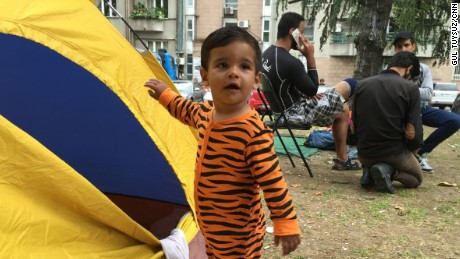 Toddler Ali is in his pajamas outside his family tent near Bristol Park in Belgrade. His family has been on the road for 10 days.