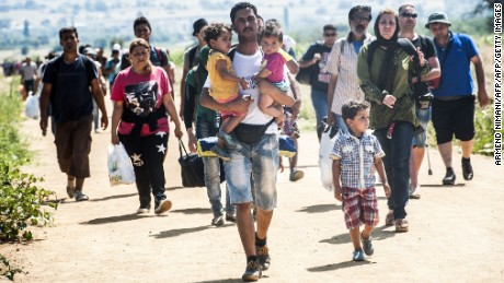 A man carries two children as he walks with other migrants near the southern Serbian village of Miratovac, travelling on foot from Macedonia to Presevo in Serbia, on August 25, 2015. At least 2,000 more migrants flooded overnight into Serbia in a desperate journey to try and go on to Hungary, the door into the European Union, a UN official said on August 24. More than 9,000 people, mostly Syrian refugees, have arrived to Serbia those last three days. AFP PHOTO / ARMEND NIMANI        (Photo credit should read ARMEND NIMANI/AFP/Getty Images)
