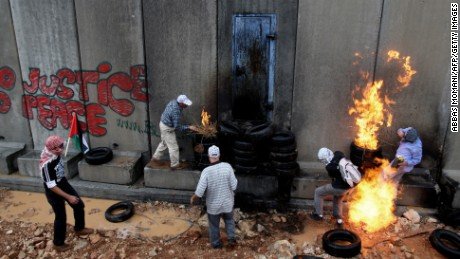 Palestinian youths set tires ablaze at Israel's separation wall in the West Bank village of Ni'lin, following a march organized by the villagers against the barrier built on village land, on October 30, 2009. Israeli Prime Minister Benjamin Netanyahu met with Washington's Middle East envoy ahead of talks with US Secretary of State Hillary Clinton aimed at reviving the moribund peace talks.  AFP PHOTO/ABBAS MOMANI (Photo credit should read ABBAS MOMANI/AFP/Getty Images)