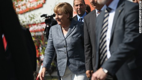 HEIDENAU, GERMANY - AUGUST 26: German Chancellor Angela Merkel arrives to visit the aslyum shelter that was the focus of recent violent protests on August 26, 2015 in Heidenau, Germany. Onlookers booed as she arrived and right-wing demonstrators clashed violently with police last weekend near the shelter. This is Merkel's first visit to a shelter for migrants seeking asylum in Germany. Germany is expecting to receive at least 800,000 migrants and refugees this year and is struggling to house them and process their asylum applications. (Photo by Sean Gallup/Getty Images)
