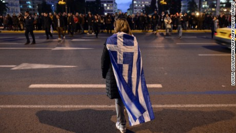 "A woman wrapped in a greek flag makes her way in front of the Greek parliament  in Athens on February 5, 2015 as people gather in support of the new anti-austerity government's efforts to renegotiate Greece's international loans. About 5,000 people gathered in Syntagma Square, police said, in front of the Greek parliament, the site of violent protests at the height of the Greek crisis in 2012. Many praised the government for ""defending the interests"" of the Greek people. AFP PHOTO/ Louisa Gouliamaki        (Photo credit should read LOUISA GOULIAMAKI/AFP/Getty Images)"
