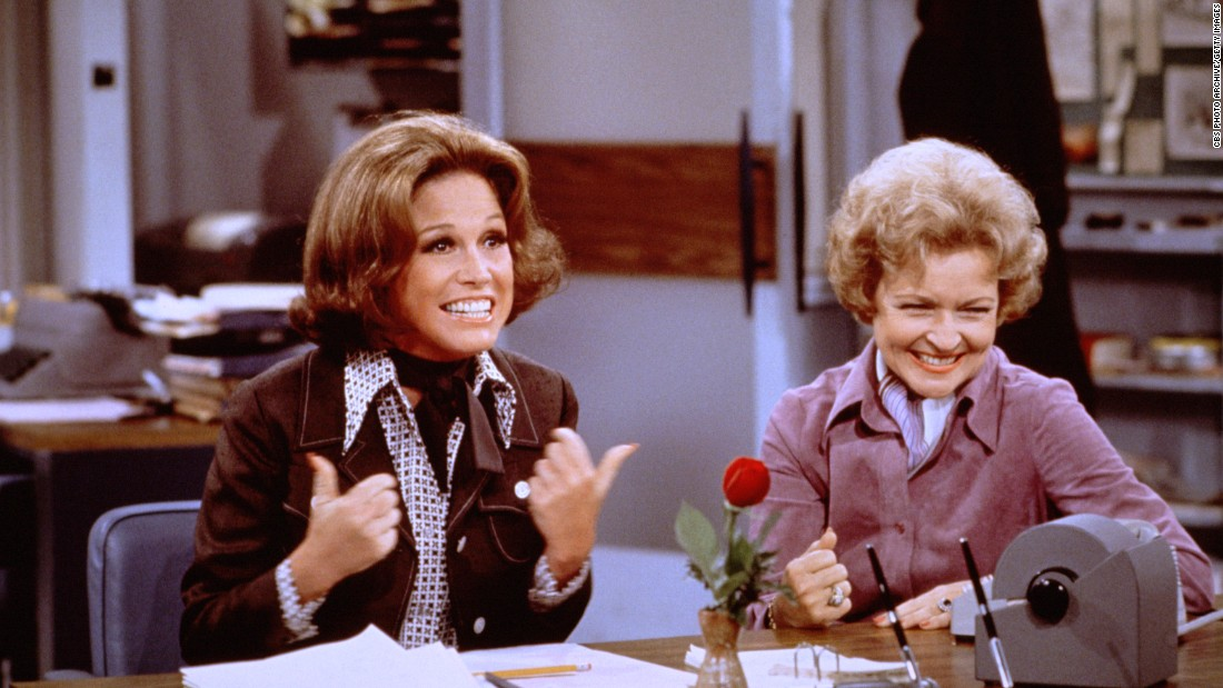 "Mary Tyler Moore (as Mary Richards) (left) gives a ""thumbs up"" sign as she sits at her desk with Betty White (as Sue Ann Nivens) in a scene from ""The Mary Tyler Moore Show"" in 1975. Nivens, the ""Happy Homemaker,"" could make a wicked Veal Prince Orloff and also cut rivals down to size."