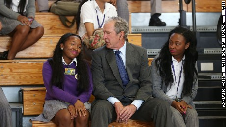 NEW ORLEANS, LA - AUGUST 28:  Former President George W. Bush sits with Ashantae Martin (L) and Ronjae Pleasant as he attends an event at Warren Easton High School to mark the 10th anniversary of Hurricane Katrina on August 28, 2015 in New Orleans, Louisiana. The former President's visit came as the town prepares to honor the tenth anniversary of Hurricane Katrina, which killed at least 1836 and is considered the costliest natural disaster in U.S. history, on August 29.  (Photo by Joe Raedle/Getty Images)