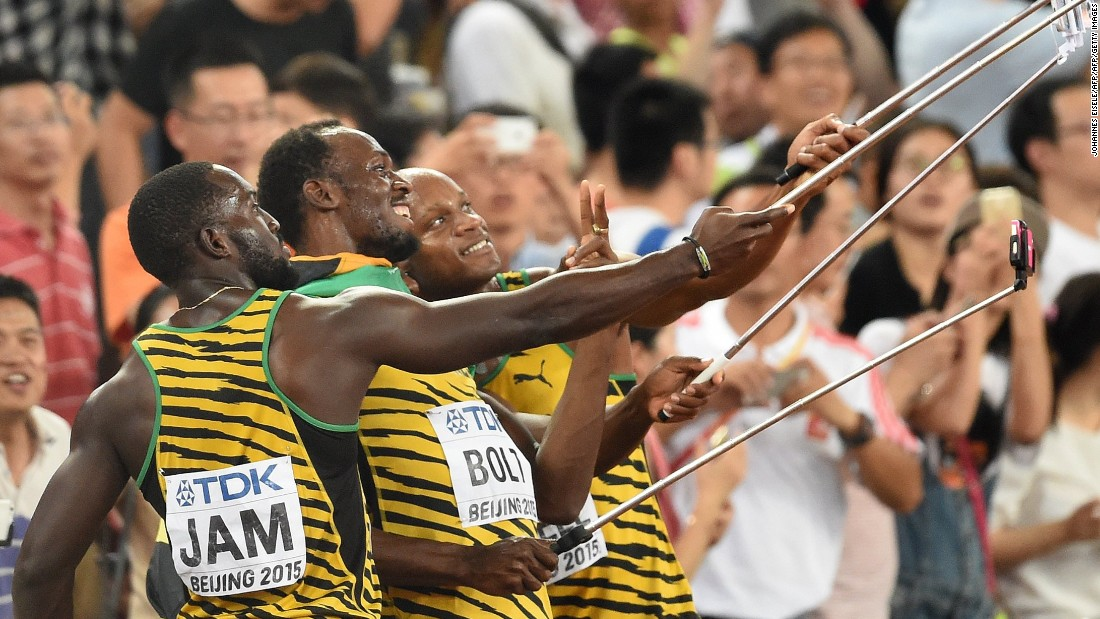 The Jamaican relay team celebrate by taking selfies with fans.