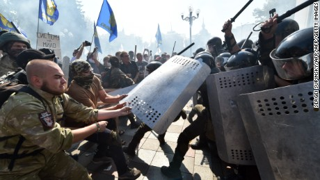 "People try to pull shields away from officers as activists of radical Ukrainian parties, including the Ukrainian nationalist party Svoboda (Freedom), clash with police officers in front of the parliament in Kiev on August 31, 2015. At least 20 were wounded in clashes outside parliament in Kiev after lawmakers gave initial approval to constitutional changes granting more autonomy to pro-Russian separatists in eastern Ukraine. A loud blast was heard outside parliament shortly after the bill was passed, an AFP journalist said. Ukrainian interior ministry advisor and top lawmaker Anton Gerashchenko wrote on Facebook that attackers threw a hand grenade at National Guard troops guarding the building in what he called an ""act of provocation."" AFP PHOTO / SERGEI SUPINSKU        (Photo credit should read SERGEI SUPINSKY/AFP/Getty Images)"