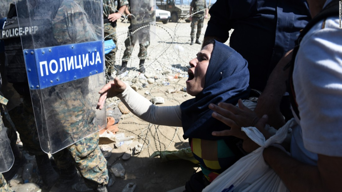 A migrant shouts at Macedonian police officers while trying to cross Greece's northern border into Macedonia. About 1,500 migrants were waiting to cross the border.