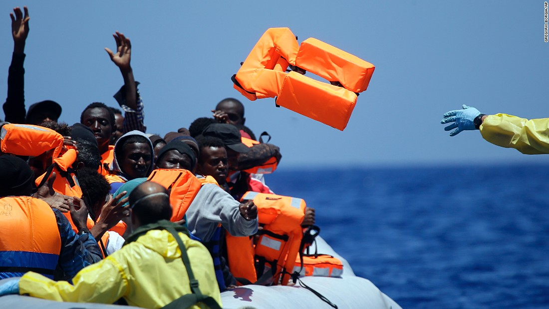 A Belgian sailor throws life vests to refugees during a search-and-rescue mission off the Libyan coast in June 2015.