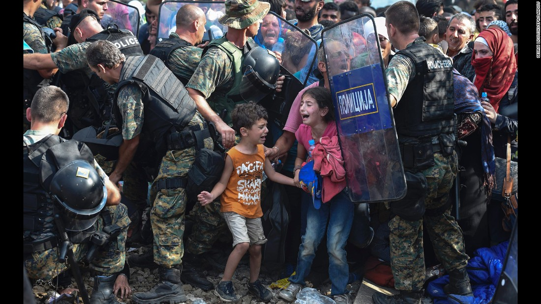 "Children cry as migrants in Greece try to break through a police cordon to cross into Macedonia in August 2015. Thousands of migrants -- most of them fleeing Syria's bitter conflict -- were stranded in a <a href=""http://www.cnn.com/2015/08/22/europe/europe-macedonia-migrant-crisis/"" target=""_blank"">no-man's land</a> on the border."