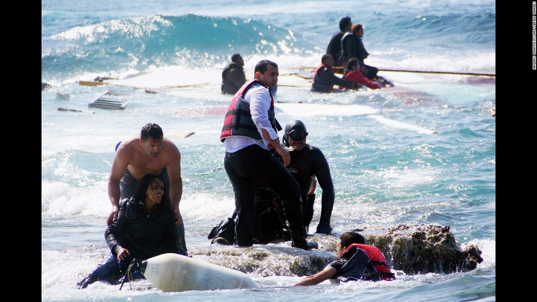 Local residents and rescue workers help migrants from the sea after a boat carrying them sank off the island of Rhodes, Greece, in April 2015.