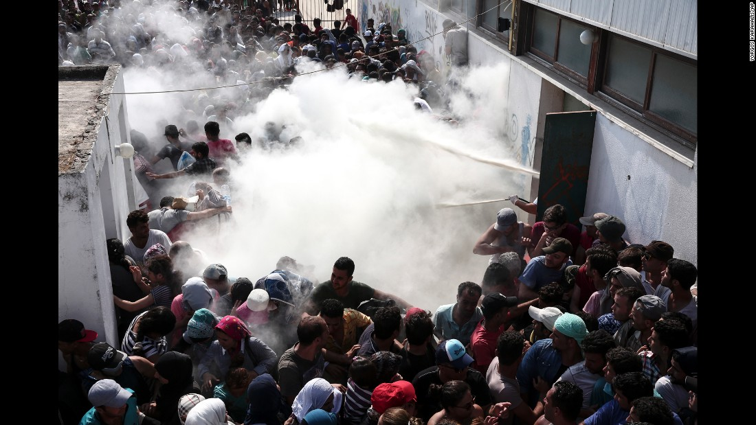 Policemen try to disperse hundreds of migrants by spraying them with fire extinguishers during a registration procedure in Kos, Greece, in August 2015.