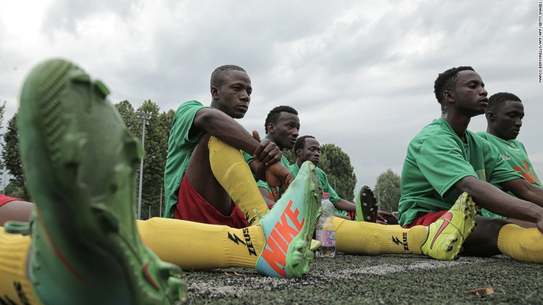 "Malian refugee Aboudala Dembele (C), rests with teammates at half-time during the match against Guinea as part of the ""Balon Mundial"" football tournament for migrants and foreigners, on June 13, 2015 in Turin."