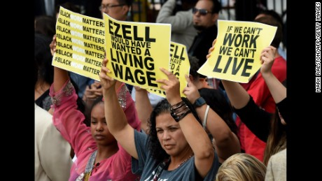 Members of the 'Black Lives Matter' group protest the death of Ezell Ford as the Los Angeles Mayor Eric Garcetti signs into law an ordinance raising the minimum wage to  USD 15 an hour by 2020, in Los Angeles, California on June 13, 2015.  Los Angeles is the first major city to sign the ordinance and the increase will be USD 6 from the current  USD 9 per hour.        AFP PHOTO / MARK RALSTON        (Photo credit should read MARK RALSTON/AFP/Getty Images)