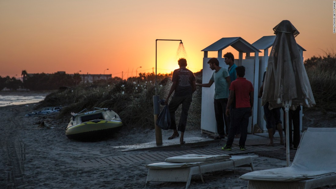 New arrivals rinse off at a beach shower at sunrise in Kos on August 30.