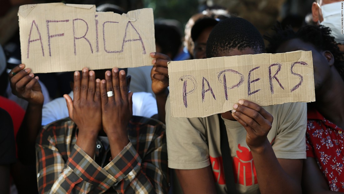 African men hold up signs urging Greek authorities to issue their official immigration papers in Kos on August 28.