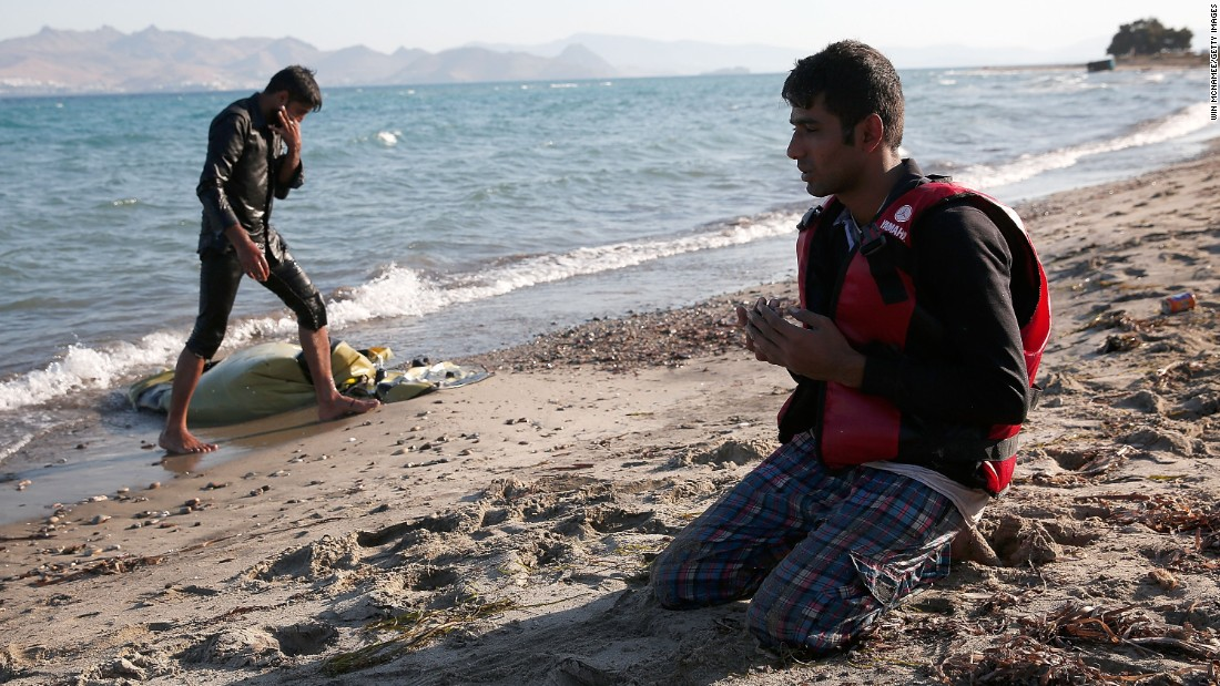 A  Pakistani man prays on the beach after safely completing his journey from Turkey to Kos on August 29.