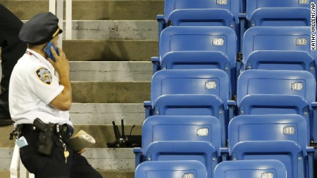 A police officers on Thursday stands beside part of a drone that crashed into an empty section of seats at the U.S. Open tennis tournament in New York.