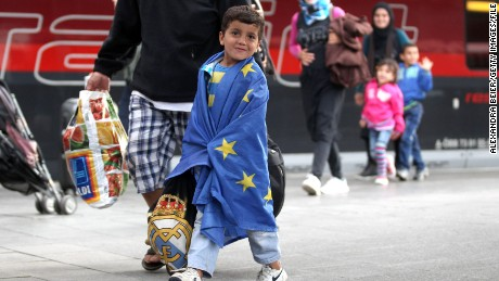 A migrant boy wrapped in an EU flag arrives in Munich, Germany, in 2015.