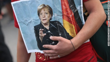 A Syrian refugee holds a picture of German Chancellor Angela Merkel as he and hundreds of others arrive in Munich.
