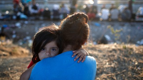 IDOMENI, GREECE - SEPTEMBER 02:  A Syrian girl is held by her mother as they wait to be processed through a border crossing into Macedonia for migrants September 2, 2015 in Idomeni, Greece.  Since the beginning of 2015 the number of migrants using the so-called 'Balkans route' has exploded with migrants arriving in Greece from Turkey and then travelling on through Macedonia and Serbia before entering the EU via Hungary. The number of people leaving their homes in war torn countries such as Syria, marks the largest migration of people since World War II.  (Photo by Win McNamee/Getty Images)