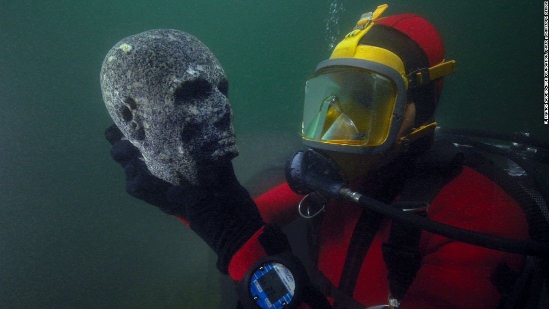 Here, a diver inspects a recovered black granite statue depicting a priest's head. The scalp is probably shaven, as was befitting of priests, for reasons of purity. The cheekbones are pronounced and the cheeks hollowed. On the forehead, the scarification mark of priests is visible and the eyes, now hollowed out, would have been incrusted with something unknown today.