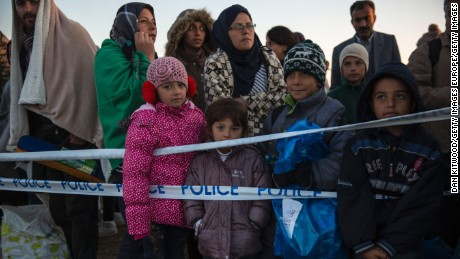 Children who had crossed into Hungary from Serbia stand at a collection point awaiting buses to take them to a refugee camp at dawn on September 8, 2015 in Morahalom, Hungary.