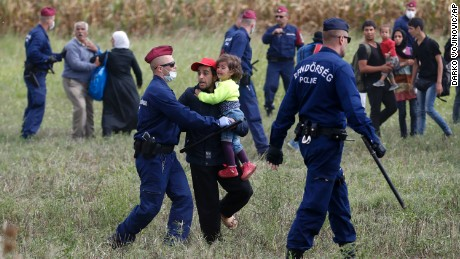Hungarian police officers stop refugees from leaving a cordoned off area in Roszke, Hungary, on September 8.
