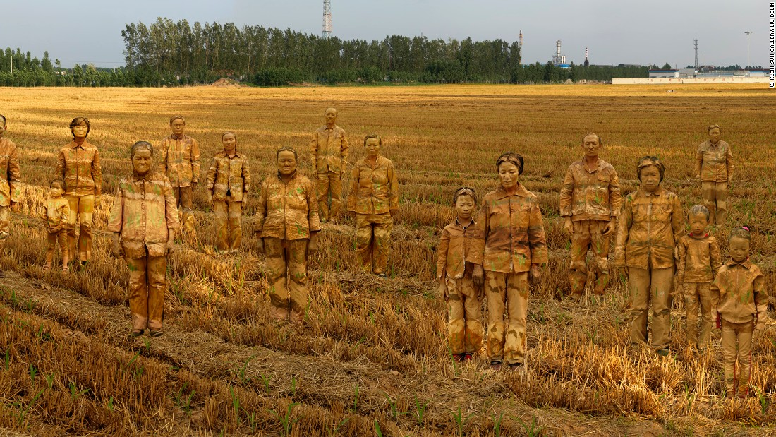"The artist work has evolved to include other people. In this piece, he paints 23 residents affected by one of China's infamous cancer villages. Chemical factories can be seen in the distance. ""When I made this work about a cancer village, my art reflected human suffering through commemoration and grief.""<br />"